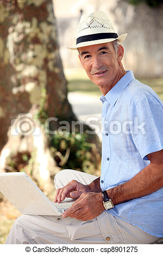 Middle-aged man sat in park with laptop - csp8901275