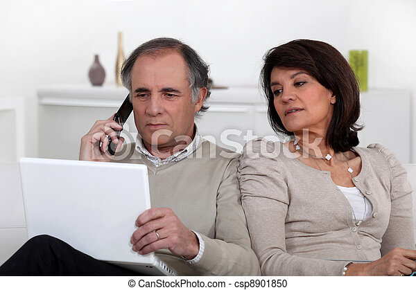 Nosy wife looking at her husband's laptop screen - csp8901850