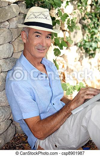 Elderly man relaxing in his garden - csp8901987