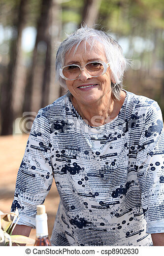 Older woman outdoors with a bottle of wine - csp8902630