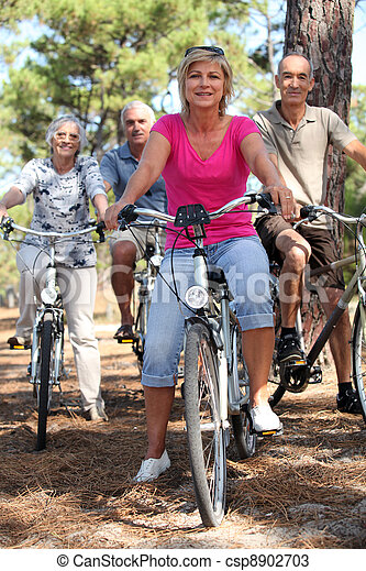 Two middle-aged couples riding bicycles - csp8902703