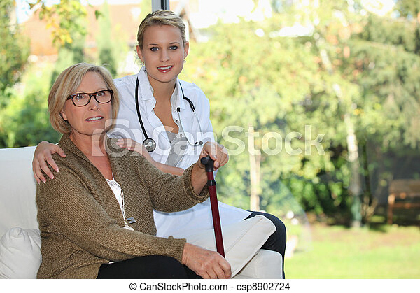 Elderly woman and young female caregiver at home - csp8902724