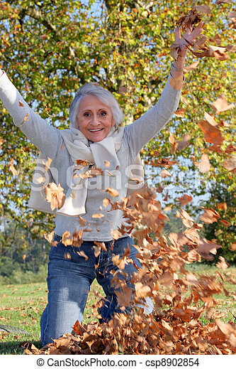 grandmother playing with a heap of dead leaves