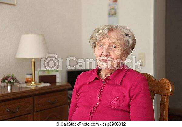 Pensioner Sitting In Chair In Livingroom - csp8906312