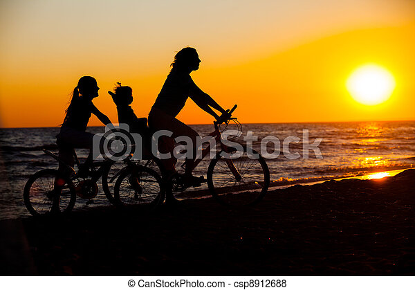 Mother and her kids on the bicycle silhouettes - csp8912688
