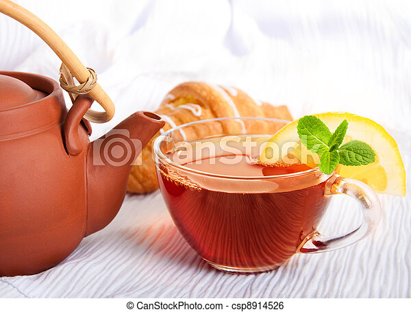 Cup of fragrant tea flowing from a ceramic teapot - csp8914526
