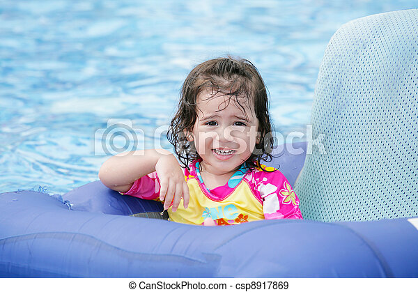 Baby girl having fun on a blue float into a tropical swimming pool  - csp8917869