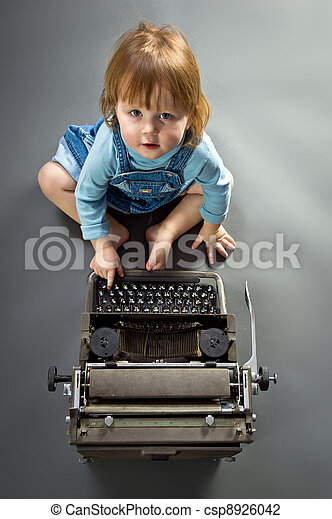 Cute little baby with retro style typewriter - csp8926042