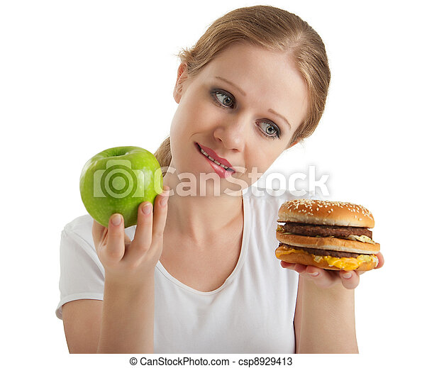 attractive young woman makes a choice between healthy and unhealthy foods, apple and hamburger isolated on white background - csp8929413