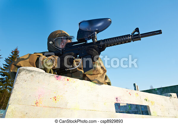 paintball player with marker at winter outdoors - csp8929893