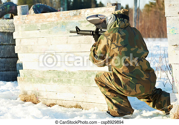 paintball player with marker at winter outdoors - csp8929894