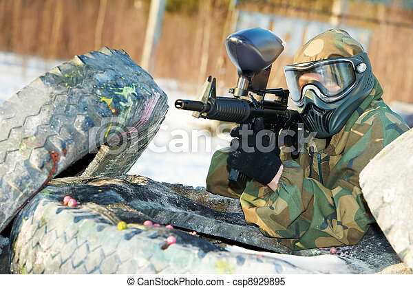paintball player with marker at winter outdoors - csp8929895