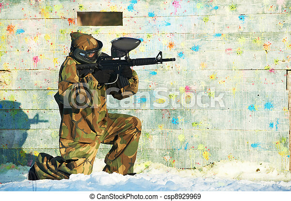 paintball player with marker at winter outdoors - csp8929969