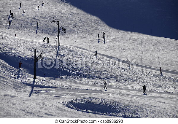 Silhouettes of skiers and tows with back lighting