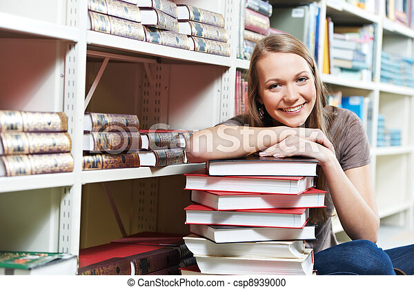 Smiling young adult woman reading  book in library - csp8939000