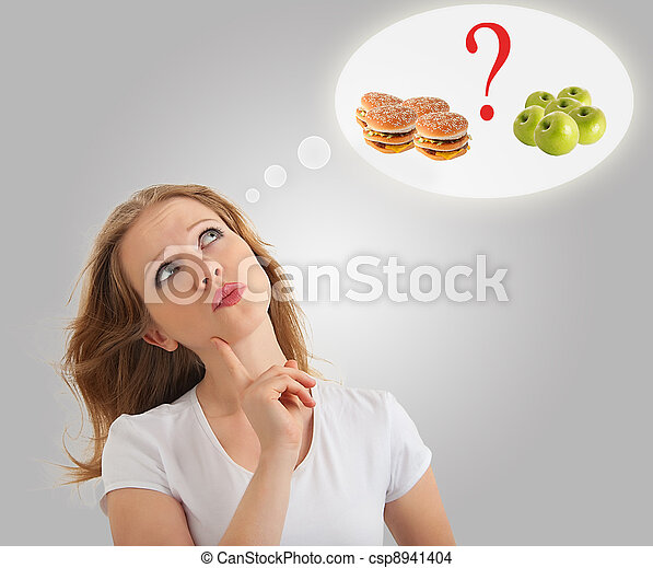 attractive young  woman makes a choice between healthy and unhealthy foods, apple and hamburger on a modern conceptual background - csp8941404