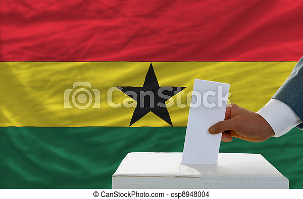 man voting on elections in ghana in front of flag - csp8948004