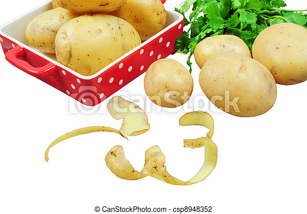 Raw potatoes in red tray and potato peels, isolated  - csp8948352