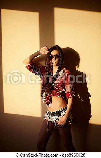 portrait of beautiful fashion sexy brunette girl in jeans and colorful shirt in glasses behind sunset indoors - csp8960428