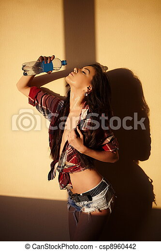 portrait of beautiful fashion sexy brunette girl in jeans and colorful shirt  behind sunset with bottle water  indoors - csp8960442