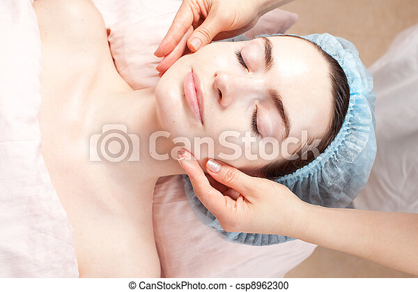 Beautiful woman with clear skin getting beauty treatment - massage of her face at salon - csp8962300