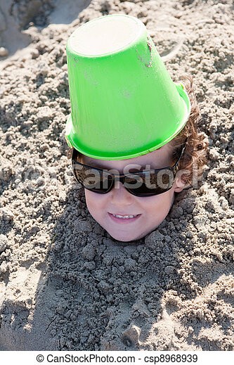 Child buried in the sand - csp8968939