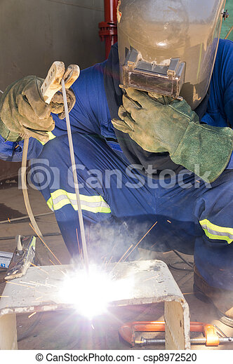 A welder with personal protective equipment welding the steel bracket - csp8972520
