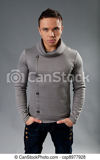 Sexy fit and neat young man in studio. Wearing grey turtleneck sweater. Fit and neat collection. - csp8977928