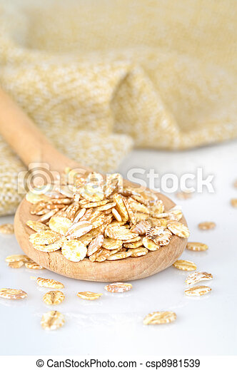 close up of oat flakes in wooden spoon  - csp8981539
