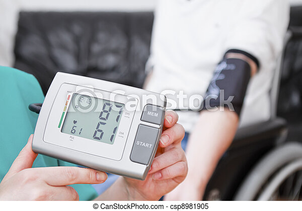 Blood pressure check for young adult in wheelchair. - csp8981905