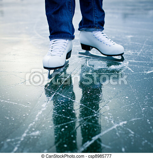 Young woman ice skating outdoors on a pond on a freezing winter day - detail of the legs - csp8985777