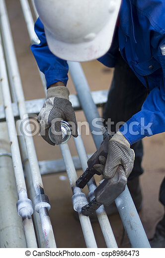 """worker with personal protective equipment checking the quality of weld joint using Magnetic Particle Inspection """"MPI"""" method - csp8986473"""