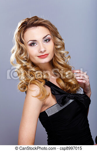 Young woman in black dress with curly hair - csp8997015