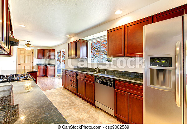 Large bright kitchen with dark cherry cabinets. - csp9002589