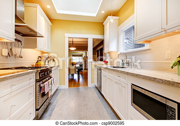Yellow and white simple kitchen with skylight. - csp9002595
