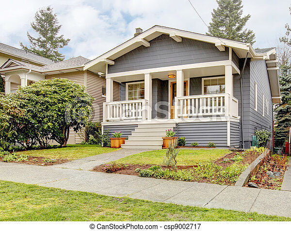 Grey craftsman style house with white porch. - csp9002717