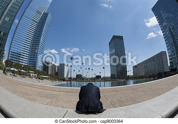 Man sitting tired and lonely in business district - csp9003364
