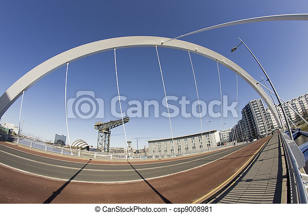 Sunshine and blue sky in Glasgow. Fisheye lens used to show span of bridge and riverfront landmarks in the background.