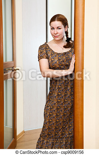 Portrait of young Caucasian female in dress standing in domestic room - csp9009156
