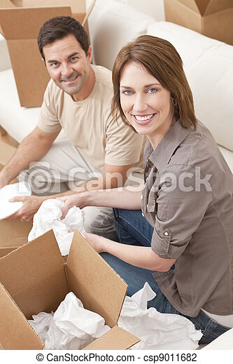 Happy Couple Unpacking or Packing Boxes Moving House - csp9011682