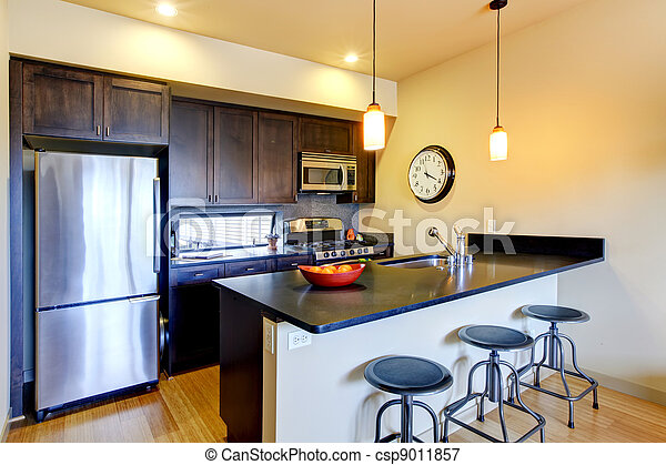 Modern brown kitchen with bar and stools. - csp9011857
