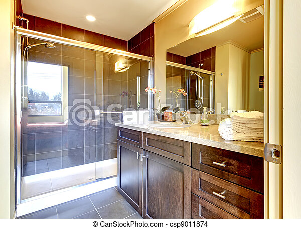 Bathroom with wood cabinet and glass shower. - csp9011874