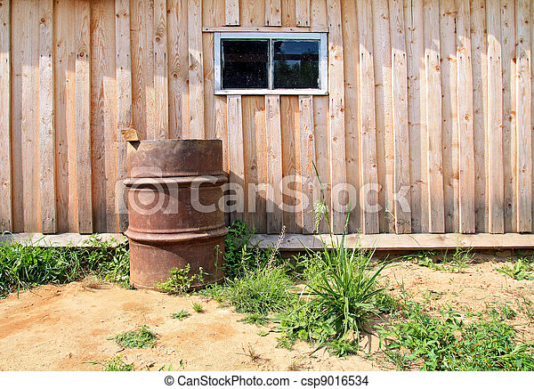 rusty barrel near wooden shed - csp9016534