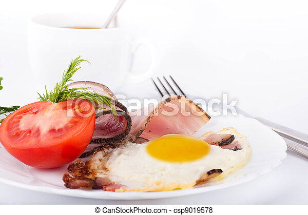 Fried eggs with bacon and tomatoes, a cup of coffee, a nourishing breakfast - csp9019578