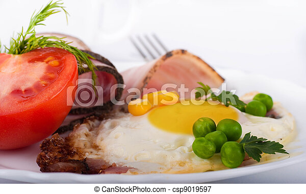 Fried eggs with bacon and tomatoes, a peas and corn, a nourishing breakfast - csp9019597