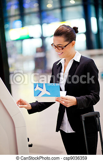 happy businesswoman using self help check in machine at airport - csp9036359