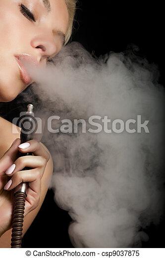 Woman smokes a hookah - csp9037875