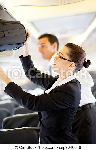 friendly flight attendant helping passenger - csp9040048