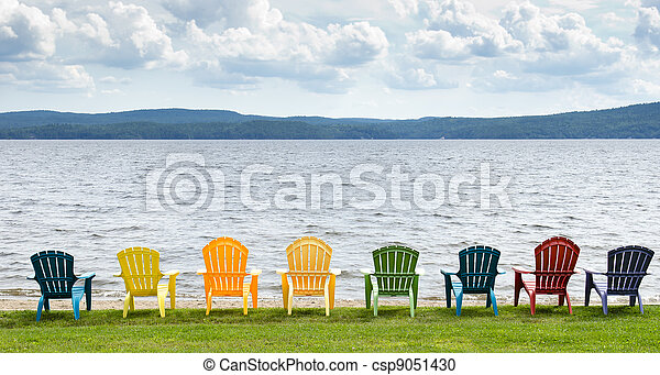 Eight colorful Adirondack chairs lined up on the beach looking out on the lake, mountains and clouds. - csp9051430