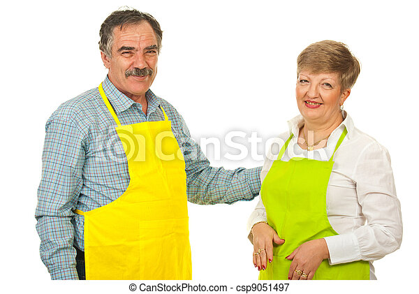 Happy mature couple with aprons - csp9051497